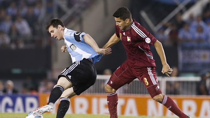 Argentina's Lionel Messi, left, fights for the ball with Venezuela's Tomas Rincon, right, during a 2014 World Cup qualifying soccer match  in Buenos Aires, Argentina,  Friday, March 22, 2013. (AP Photo/Victor R. Caivano)