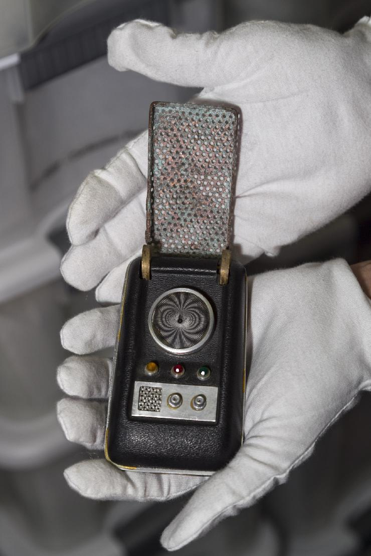In this Friday, Nov. 30, 2012 photo, James Comisar holds a communicator prop used on the original Star Trek series. The item is part of his television memorabilia collection in a temperature- and humidity-controlled warehouse in Los Angeles. (AP Photo/Damian Dovarganes)