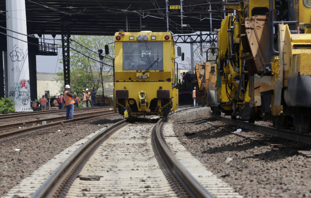 Metro North railroad employees use heavy equipment to repair tracks near Bridgeport, Conn., Monday, May 20, 2013. A train collision on Friday injured 72 people and disrupted rail service into New York