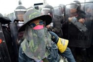 <p>An anti-government protester stands in front of riot policemen during a protest in Bangkok on November 24. The no-confidence debate kicked off a day after riot police clashed with anti-government protesters in Bangkok.</p>