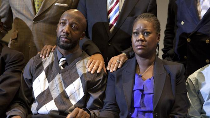 FILE- In this April 11, 2012 file photo, the parents of Trayvon Martin, Sybrina Fulton, right, and Tracy Martin hold hands as they watch a news conference in Washington with special prosecutor Angela Corey announcing charges against George Zimmerman. The central Florida suburb of Sanford, Fla. is getting back to normal a year after Zimmerman shot and killed Martin in a gated community.  (AP Photo/Evan Vucci, Pool, File)