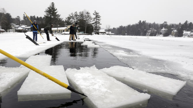 A volunteer moves blocks of ice that have been cut from Lake Flower that will be used for the Saranac Lake Winter Carnival ice palace on Monday, Jan. 28, 2013, in Saranac Lake, N.Y. (AP Photo/Mike Groll)