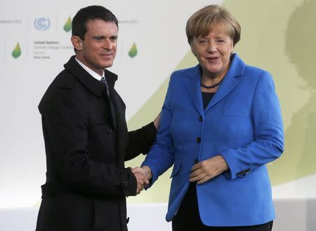 French Prime Minister Valls welcomes German Chancellor Merkel as she arrives for the opening day of the World Climate Change Conference 2015 (COP21) at Le Bourget, near Paris