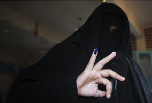 An Egyptian woman holds up her inked pinky finger that shows she has voted at a polling station in the town of Ibshawai, near Fayoum, 100 km (62 miles) southwest of Cairo, Egypt, Tuesday, Nov. 29, 2011. Polls opened Tuesday for a second day of voting in Egypt's landmark parliamentary elections, the first since Hosni Mubarak's ouster in a popular uprising earlier this year. (AP Photo/Tara Todras-Whitehill)
