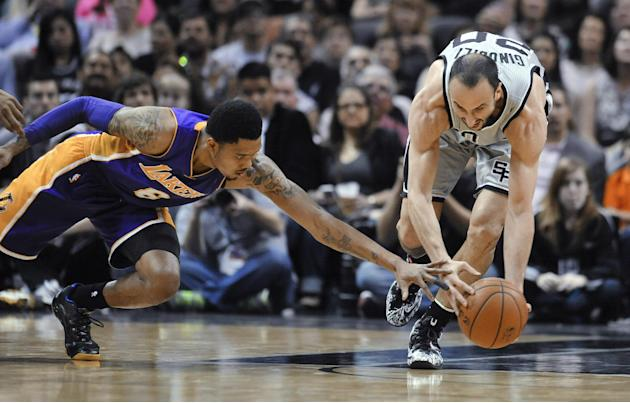 San Antonio Spurs guard Manu Ginobili, right, comes up with a loose ball in front of Los Angeles Lakers guard Kent Bazemore during the first half of an NBA basketball game Friday, March 14, 2014. (AP