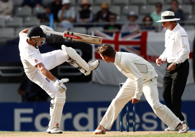 Compton of England loses his balance after being hit by the ball watched by New Zealand's Martin and umpire Rod Tucker during day two of their final cricket test match at Eden Park in Auckland