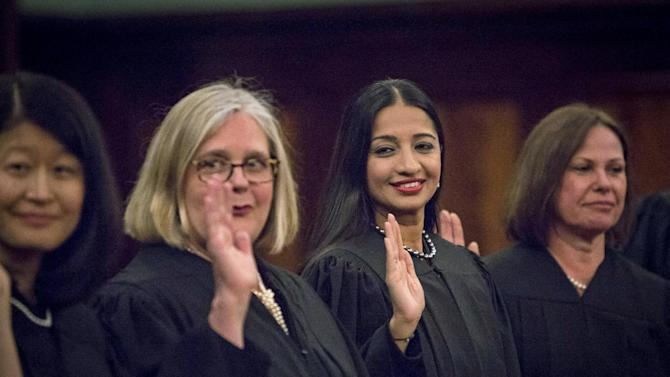 Newly appointed city judge Raja Rajeswari from Chennai in India raises her right hand during a Judicial Swearing-In Ceremony at New York City Hall in New York