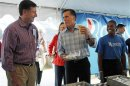 Republican presidential candidate and former Massachusetts Governor Mitt Romney talks to former U.S. Senator George Allen while eating a hotdog at the Federated Auto Parts 400 NASCAR Sprint Cup Series race in Richmond