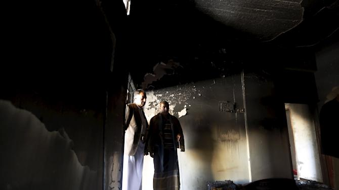People look at damage in a house caused by an air strike that hit a nearby army weapons depot in Sanaa