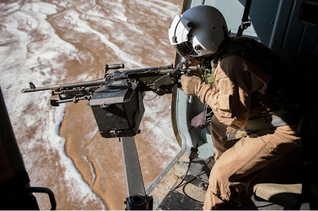 Afghan air force Sgt. Razeg, a gunner, fires an M-240 weapon from an Mi-17 Helicopter during a mission from Kabul, Afghanistan. The flight was a