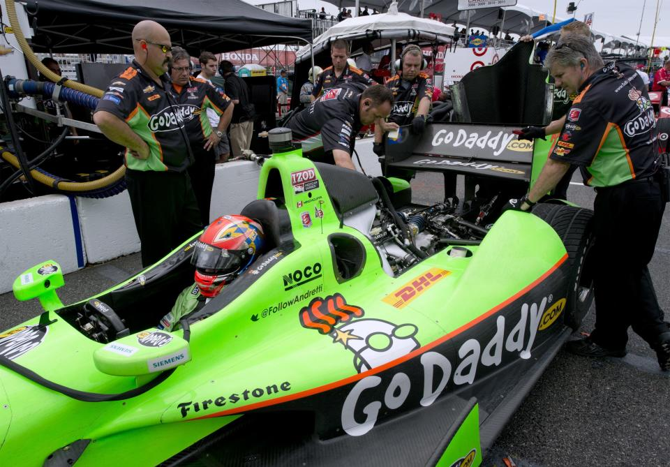 James Hinchcliffe sits as mechanics work on his car during the morning practice session for the Toronto Indy auto race in Toronto on Saturday, July 7, 2012. (AP Photo/The Canadian Press, Frank Gunn)