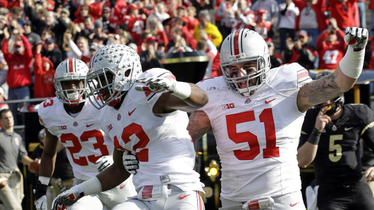 Ohio State cornerback Doran Grant, center, celebrates with defensive tackle Joel Hale (51) and defensive back Tyvis Powell after returning an interception for a touchdown during the first half of an NCAA college football game against Purdue Saturday, Nov. 2, 2013, in West Lafayette, Ind. (AP Photo/Michael Conroy)