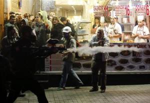 Customers and cooks inside a kebab shop watch as a riot police officer fires plastic paintball gun pellets to disperse demonstrators during an anti-government protest in central Istanbul