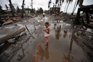 A child stands in a street lined with destroyed buildings following days of sectarian violence in Sittwe, capital of Myanmar&#39;s Rakhine state, in June. Charred stumps and scattered rubbish are all that remain of a once-bustling community in strife-torn western Myanmar, just one of many razed to the ground in recent communal violence