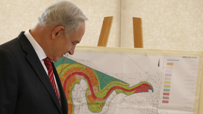 Israeli Prime Minister Benjamin Netanyahu looks at a map of the area where Israel plans to build some 800 new housing units during his visit to the east Jerusalem Jewish neighborhood of Gilo, Tuesday, Oct. 23, 2012. Netanyahu vowed on Tuesday to continue building in the Jerusalem district days after European Union criticism because it is claimed by Palestinians. (AP Photo/Gali Tibbon, Pool)