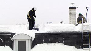 Workers remove snow and ice from a rooftop in Ottawa.