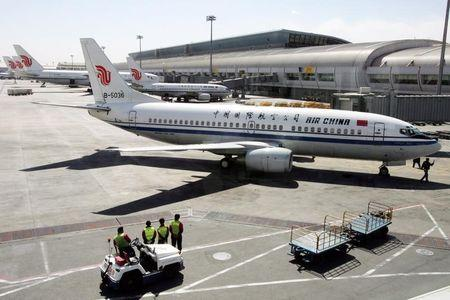 Chinese workers check Air China aircrafts at Beijing Airport.