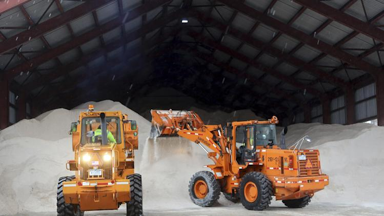 Sanitation workers use tractors to pile up salt at a depot, Friday, Feb. 8, 2013 in New York. A storm poised to dump up to 3-feet of snow from New York City to Boston and beyond beginning Friday could be one for the record books, forecasters warned, as residents scurried to stock up on food and water and road crews readied salt and sand. (AP Photo/Mary Altaffer)