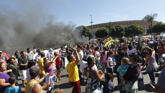Demonstrators protest outside the National Stadium in Brasilia, Brazil, Friday, June 14, 2013. About 200 people burned tires and blocked the main road in front of the Brasilia stadium which will host the Confederations Cup opening match between Brazil and Japan on June 15.The protest was organized by several local groups complaining of the excessive costs of the Confederations Cup and the World Cup. (AP Photo/Andre Penner)