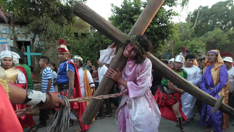 An actor playing the role of Jesus Christ carries a cross as he takes part in a re-enactment of the crucifixion of Jesus Christ during Holy Week in Masaya