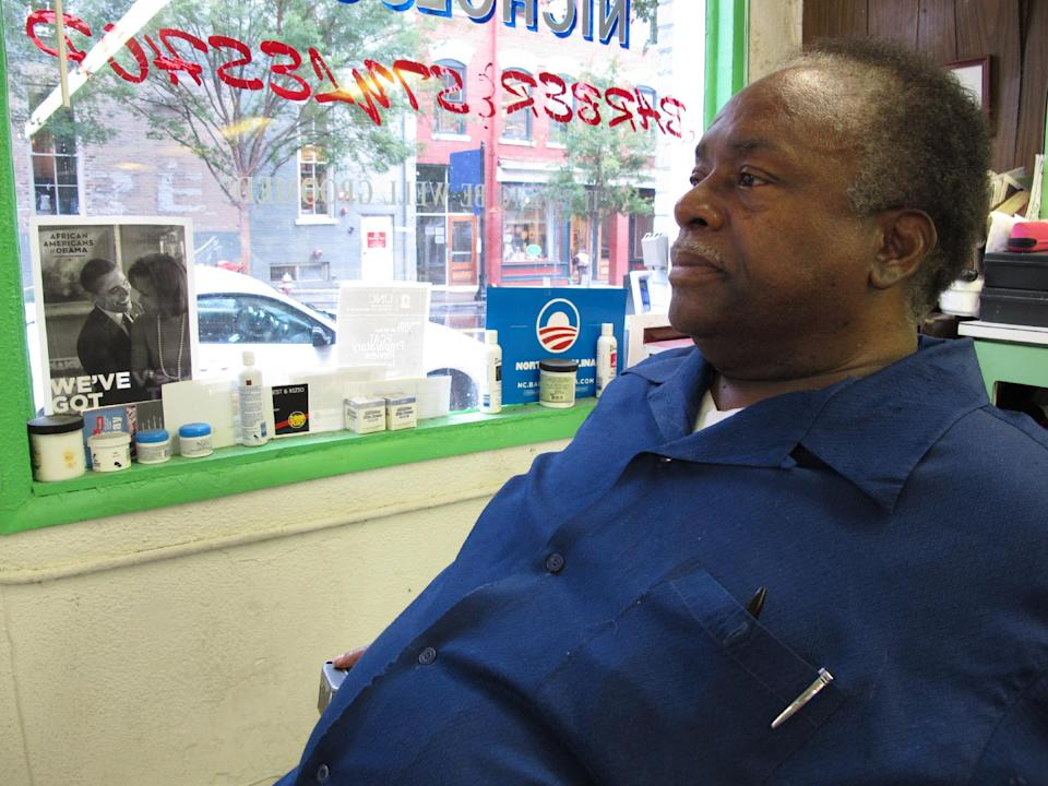 In this Wednesday, Aug. 22, 2012 photo, Carlton Nicholson sits in his empty barber shop in downtown Raleigh, N.C. The black vote helped Barack Obama become the first Democrat in a generation to take the state, but Nicholson worries the bad economy will cost him this time around. (AP Photo/Allen Breed)