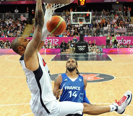 United States&#39; center Tyson Chandler, left, hangs on the hoop in front of French center Ronny Turiaf during the men&#39;s basketball preliminary round group A match between the United States and France at the 2012 Summer Olympics, on Sunday, July 29, 2012 in London. (AP Photo/Mark Ralston, Pool)