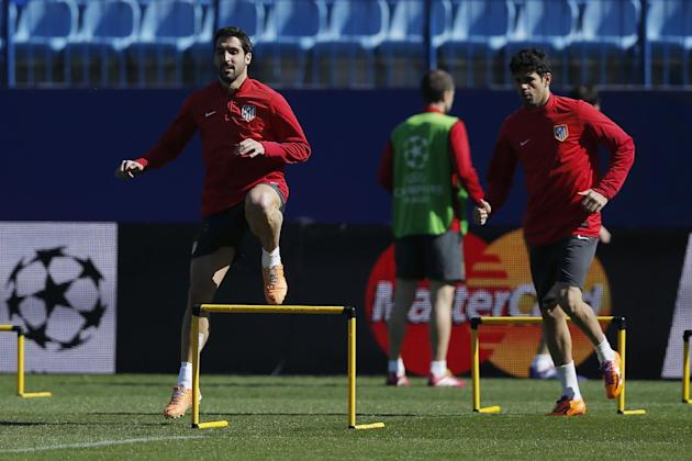Atletico Madrid Diego Costa, right, and Raul Garcia, left, exercise during a training session ahead of Tuesday's Champions League, round of 16, second leg, soccer match against AC Milan, at the Vi