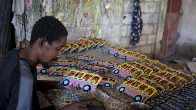 In this Dec. 9,  2012 photo, an artists paints arts and crafts at the Ajoupas Shop in Croix-des-Bouquets, Haiti. The artisan industry is enjoying an outright resurgence as it's boosted by artisan advocacy groups that are helping organize workers and improve quality. (AP Photo/Dieu Nalio Chery)