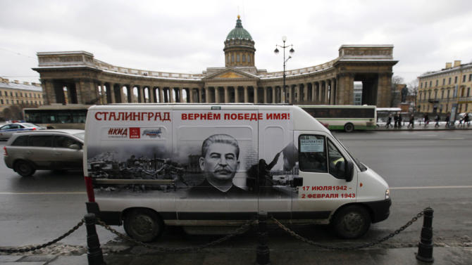 """A bus decorated with a portrait of Soviet dictator Josef Stalin and a sign reading """"Stalingrad gets back its victorious name"""" rides in front of  the Kazansky Cathedral in St. Petersburg, Russia, Saturday, Feb. 2, 2013. On Saturday Russia marked the 70th anniversary of the end of  the battle of Stalingrad. The city was renamed Volgograd in 1961, but the name Stalingrad is indelibly connected with the battle that is one of Russia's most-lauded military achievements. Stalin's image adorns five buses that are to run in Volograd until Russia observes Victory Day on May 9, and similar buses were to run Saturday in St. Petersburg and Chita. (AP Photo/Elena Ignatyeva)"""
