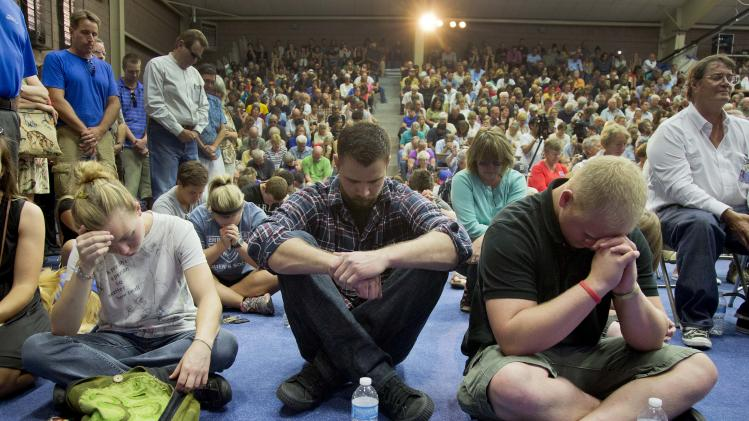 Mourners bow their heads in prayer during a memorial service, Monday, July 1, 2013 in Prescott, Ariz. The service was held for the 19 Granite Mountain Hotshot Crew firefighters who were killed Sunday, when an out-of-control blaze overtook the elite group. (AP Photo/Julie Jacobson)