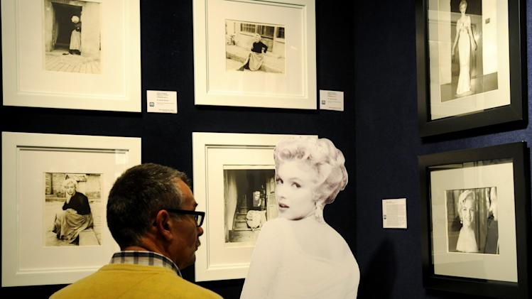 A potential bidder looks at Marylin Monroe photos prior to an auction of pictures by the late celebrity photographer Milton H. Greene, in Warsaw, Poland, Thursday, Nov. 8, 2012. Some 238 pictures by Greene including portraits of Marylin Monroe, along with Cary Grant, Frank Sinatra, Audrey Hepburn, Liza Minnelli, Marlene Dietrich, Paul Newman, Alfred Hitchcock and Marlon Brando, were auctioned off in Warsaw with highest bids reaching 60.000 Polish zlotys (18.700 US dollars, or 14.400 euros) . Proceeds from the auction will go to the Polish state which owns a collection of around 4,000 pictures by Greene that ended up in Poland's possession as the result of a complex embezzlement scandal that shook the country in the early 1990s.  (AP Photo/Alik Keplicz)