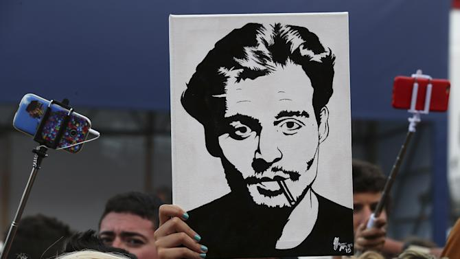 Girl holds up a portrait of actor Johnny Depp in front of the entrance of the venue of the 72nd Venice Film Festival