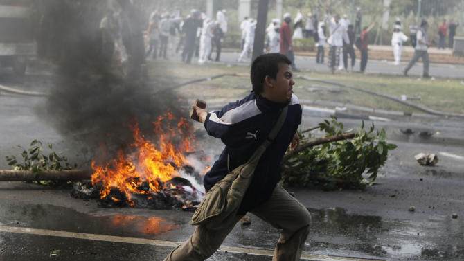 """A Muslim man prepares to throw a rock at police officers during a protest against American-made film """"Innocence of Muslims"""" that ridicules Islam and depicts the Prophet Muhammad as a fraud, a womanizer and a madman, outside the U.S. Embassy in Jakarta, Indonesia, Monday, Sept. 17, 2012. (AP Photo/Dita Alangkara)"""