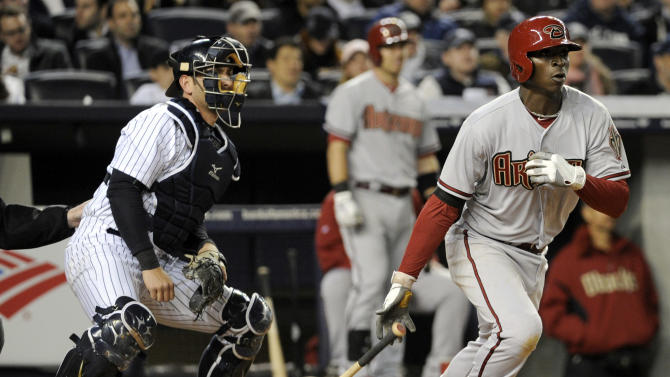 Arizona Diamondbacks' Didi Gregorius hits a double as New York Yankees catcher Francisco Cervelli, left, watches during the fifth inning of a baseball game, Thursday, April 18, 2013, at Yankee Stadium in New York. (AP Photo/Bill Kostroun)