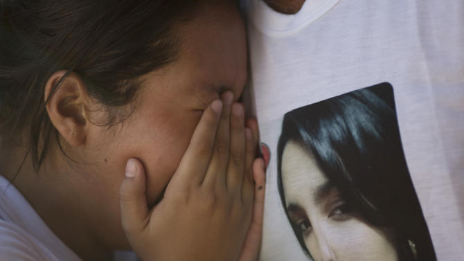 A young woman weeps as she is embraced by an unidentified man wearing a T-shirt with an image of the crying woman's sister, a victim of the Kiss nightclub fatal fire, during a protest in Santa Maria, Brazil, Tuesday, Jan. 29, 2013. Locals marched through Santa Maria Tuesday to demand justice for the dead. The demonstration interrupted a news conference as the police investigator pledged to investigate everyone involved in the tragedy - including the authorities charged with making sure such establishments are up to code. The fast-moving fire roared through the crowded, windowless Kiss nightclub in this southern Brazilian city early Sunday, killing more than 230 people.  (AP Photo/Felipe Dana)