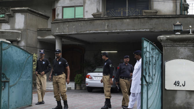Pakistani police officers gather at the entry gate of the house of an abducted American citizen in Lahore, Pakistan on Saturday, Aug. 13, 2011. Gunmen abducted an American man after raiding his home in the eastern Pakistani city of Lahore on Saturday, Pakistani officials said, an unusually brazen attack on a foreigner in a country where kidnappings are believed to help fund Islamist militant movements. (AP Photo/K.M. Chaudary)