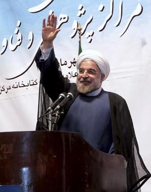 In this photo released by the official website of the office of the Iranian Presidency, Iran's President Hassan Rouhani waves to participants while he attends a ceremony to mark the beginning of the universities academic year, at the Tehran University, in Tehran, Iran, Monday, Oct. 14, 2013. Iran's president stepped up his challenge to hard-line factions on Monday, calling for the lifting of restrictions on academic freedoms and for granting Iranian scholars more opportunity to take part in international conferences. (AP Photo/Presidency Office, Ebrahim Seyyedi)