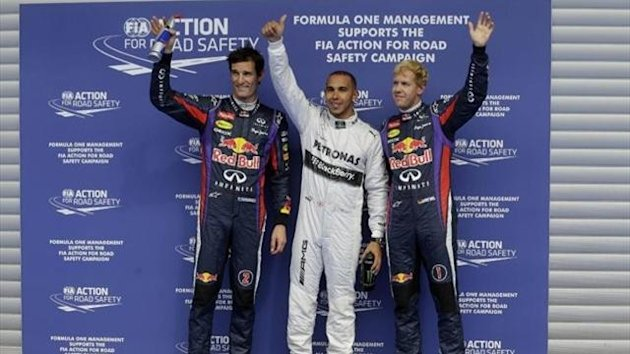 Mercedes driver Lewis Hamilton of Britain, center, pole position, Red Bull driver Sebastian Vettel of Germany, right, second fastest time, and Red Bull driver Mark Webber of Australia, left, third fastest time gesture to spectators after the qualifying se