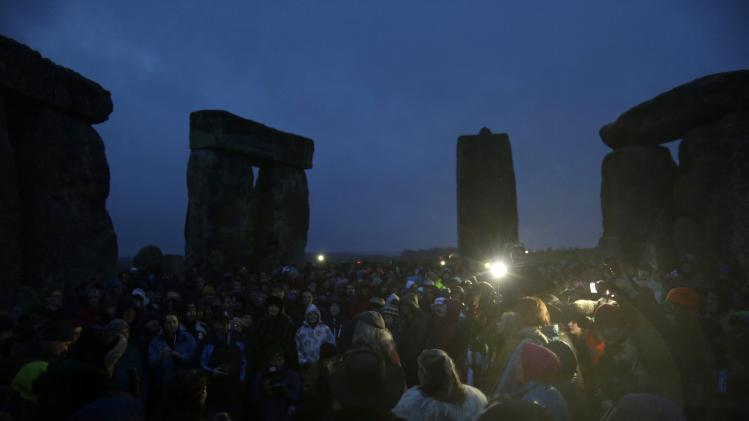Druids and revellers sing incantations as they celebrate the winter solstice at Stonehenge in Amesbury, southern England
