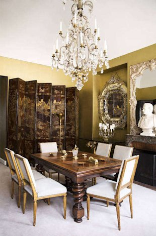 A crystal-encrusted gilt Venetian mirror hovers above a grand walnut table