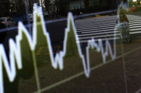 A woman pushing  cart is reflected on electronic board showing graph of recent fluctuations of Japan's Nikkei average outside a brokerage in Tokyo