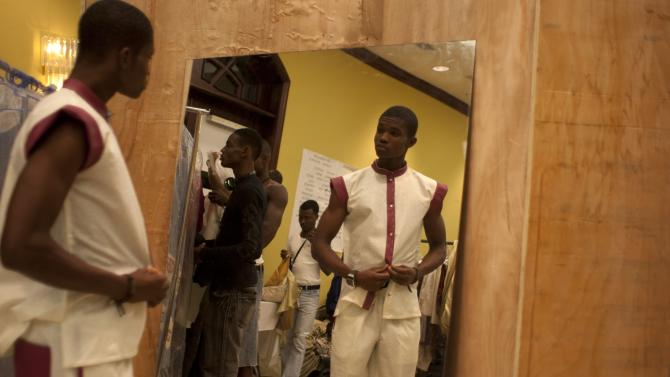 A model prepares in front of a mirror backstage before Haiti Fashion Week in Port-au-Prince, Haiti, Saturday, Nov. 10,  2012. (AP Photo/Dieu Nalio Chery)