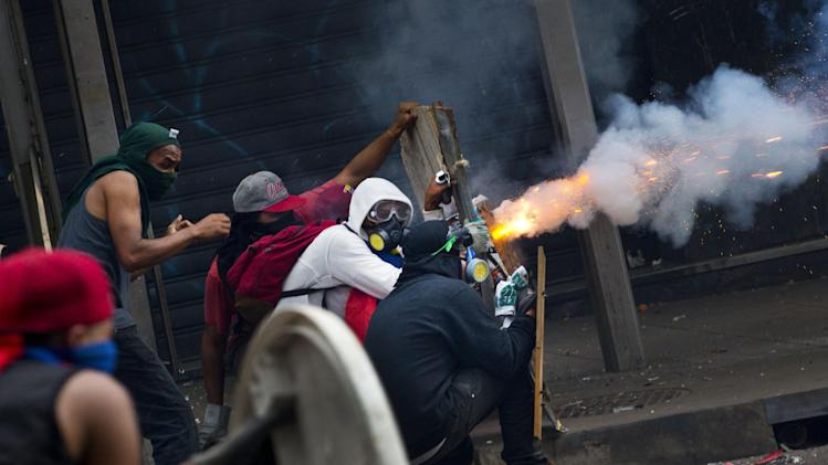 Masked anti-government protesters launch fireworks at the Bolivarian National Police during clashes in Caracas, Venezuela, Thursday, April 17, 2014. Opposition protesters have been demonstrating against high crime, high inflation and shortages of basic goods since mid-February. (AP Photo/Ramon Espinosa)