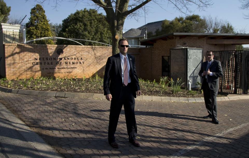 U.S. Secret Service agents stand guard outside the Nelson Mandela Centre of Memory as U.S. President Barack Obama visits the family of the former South African president and anti-apartheid hero Nelson Mandela on Saturday, June 29, 2013, in Johannesburg, South Africa. (AP Photo/Evan Vucci)