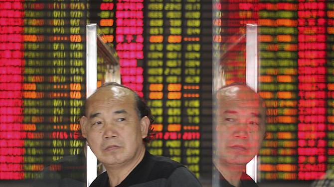 An investor is reflected on glass doors as he walks past in front of an electronic board showing stock information at a brokerage house in Shanghai