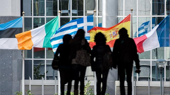 People walk in front of flags of European countries outside the European Parliament in Brussels, Friday, Oct. 12, 2012. The European Union won the Nobel Peace Prize on Friday for its efforts to promote peace and democracy in Europe, despite being in the midst of its biggest crisis since the bloc was created in the 1950s. (AP Photo/Geert Vanden Wijngaert)