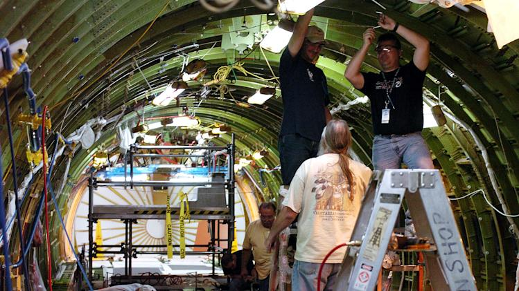 FILE - In this April 29, 2004 file photo, Boeing employees do modification work on the upper portion of a Boeing KC-767 tanker being modified for Italy at the plant in Wichita, Kan. The Boeing Co. has told its employees Wednesday, Jan. 4, 2012, that it plans to close its massive defense plant in Wichita before the end of 2013 in a bid to cut costs in a tight market for defense spending. (AP Photo/Larry W. Smith, File)