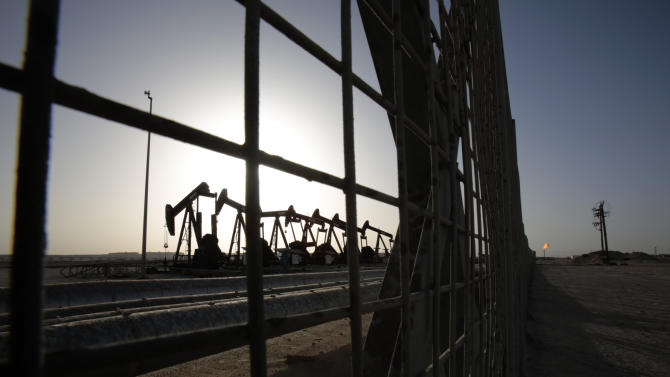 FILE - In this May 28, 2015 file photo, oil pumps work in the desert oil fields of Sakhir, Bahrain. A slew of global economic and geopolitical factors are working to pummel the price of oil and set up U.S. drivers for very low gasoline prices later this year. (AP Photo/Hasan Jamali, File)