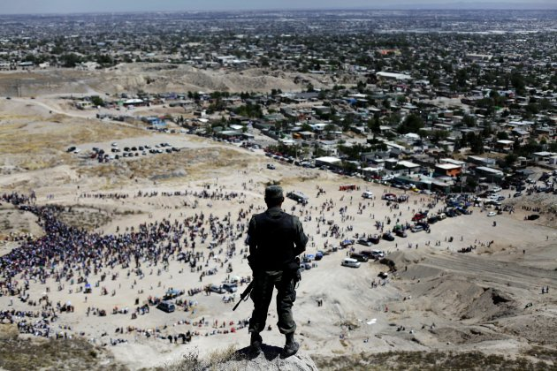 In this April 10, 2009 file photo, a soldier stands guard on the top of a hill as faithful commemorate Good Friday during Holy Week in Ciudad Juarez, Mexico. Killings by criminal gangs in the drug violence-wracked border city of Ciudad Juarez fell by 42 percent in the first six months of this year from the same period of 2011, Mexicoís army said Wednesday July 11, 2012. (AP Photo/Rodrigo Abd)