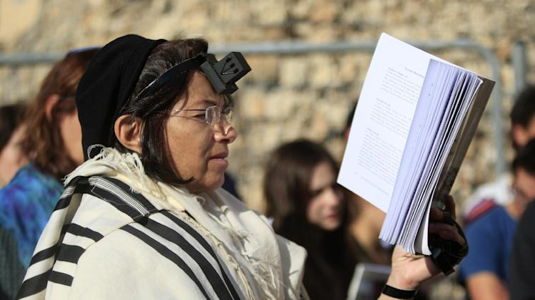Israeli women of the Women of the Wall organization pray just outside the Western Wall, the holiest site where Jews can pray in Jerusalem's old city, Friday, Dec. 14, 2012. Security guards at the Western Wall, the holiest place where Jews can pray, usually search worshippers for weapons upon entering. But on Friday, they were on the lookout for a seemingly inoffensive possession: Jewish prayer shawls. The shawls are ubiquitous at the holy site, and under Orthodox tradition, are worn only by men. When several dozen women draped in them attempted to enter the area, their multicolored garments were confiscated. (AP Photo/Dan Balilty)